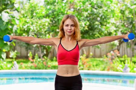 Femme sportive active faisant des exercices du matin avec des haltères à la maison. Plan d'entraînement pour obtenir un corps de plage d'été. Mode de vie sain, exercices de conditionnement physique pour garder la forme, perdre du poids et façonner un corps mince parfait. Banque d'images - 76768693