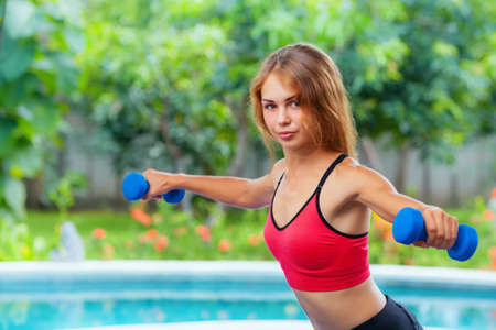 Active sporty woman doing morning exercises with dumbbells at home. Workout plan to get summer beach body. Healthy lifestyle, fitness exercises to keep fit, loss weight and shaping perfect slim body.