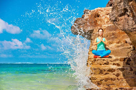 Meditation on sea surf with splashes background. Active woman sit on beach rock and practicing yoga to keep fit and health. Healthy lifestyle, fitness training, sport activity on summer family holiday Stock Photo