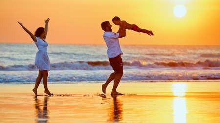 행복한 가족 - 아버지, 어머니, 아기가 아들 검은 모래 해변에서 일몰 바다 서핑의 가장자리를 따라 재미와 함께 산책. 발리 섬에 아이들과 함께 여름  스톡 콘텐츠