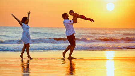 Happy family - father, mother, baby son walk with fun along edge of sunset sea surf on black sand beach. Active parents and people outdoor activity on summer vacations with children on Bali island
