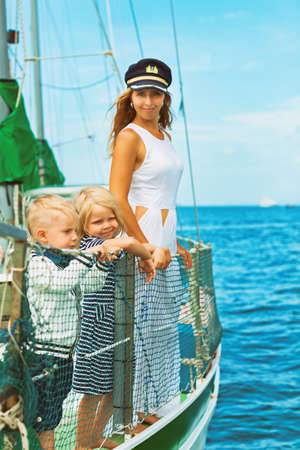 Happy family - mother in captain cap, baby son, daughter on board of sailing yacht. Children have fun discovering islands in summer cruise. Travel adventure, yachting with kids on family vacation. photo