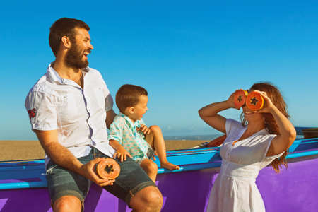 Happy funny family - father, mother, baby son walk together by sea sand beach. People have picnic - eat tropical fruit papaya with fun. Travel, active lifestyle, parents with child on summer holiday. photo