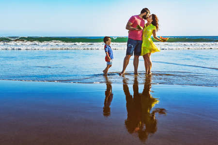 Happy family - father, mother, baby son walk by water pool on black sand beach with sea surf. People have picnic - eat tropical fruits. Travel, active lifestyle, parents with child on summer vacation. photo