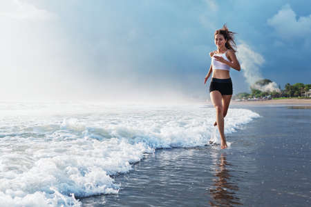 Active sporty woman run along ocean surf by water pool to keep fit and health. Sunset black sand beach background with sun. Woman fitness, jogging training and sport activity on summer family holiday. Foto de archivo