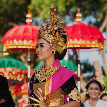 DENPASAR, BALI ISLAND, INDONESIA - JUNE 11, 2016: Beautiful woman dancer in bright traditional costume. Balinese people dancing on street parade at art and culture festival.