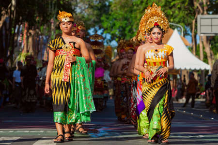 seminyak: DENPASAR, BALI ISLAND, INDONESIA - JUNE 11, 2016: Group of beautiful women and men dancers in bright traditional costume. Balinese people dancing on street parade at art and culture festival.
