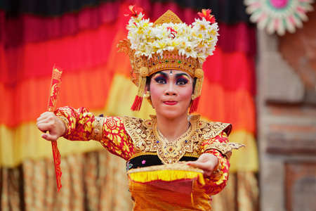 DENPASAR, BALI ISLAND, INDONESIA - JUNE 23, 2016: Face portrait of beautiful young Balinese woman in ethnic dancer costume, dancing traditional temple dance Legong at art and culture festival parade.
