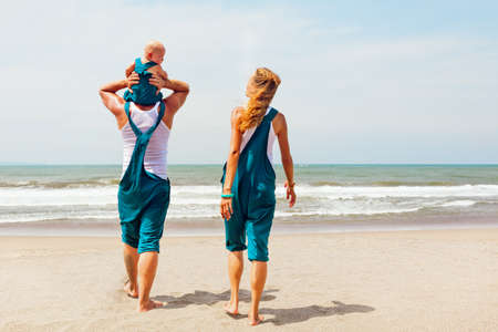 Funny portrait of happy family. People walk with fun along sea surf on sunny beach. baby son sit on father shoulders, look at mother. Leisure activity on summer vacation with child on tropical island.