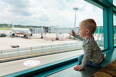 Little baby boy waiting boarding to flight in airport transit hall and looking through the window at airplane near departure gate. Active family lifestyle, travel by air with child on summer vacation photo