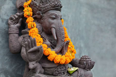 Ganesha with balinese Barong masks sitting on front of temple. Decorated for religious festival by orange flowers necklace and ceremonial offering. Travel background, Bali island art and culture.