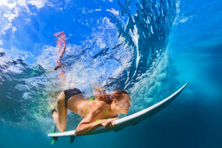 Active girl in bikini in action. Surfer woman with surf board dive underwater under breaking big wave. Healthy lifestyle. Water sport, extreme surfing in adventure camp on family summer beach vacation