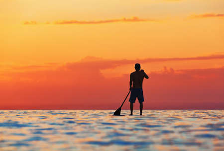 Paddle boarder. Black sunset silhouette of young sportsman paddling on stand up paddleboard. Healthy lifestyle. Water sport, SUP surfing tour in adventure camp on active family summer beach vacation.