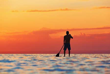 Paddle boarder. Zwarte zonsondergang silhouet van jonge sportman peddelen op opstaan paddleboard. Gezonde levensstijl. Watersport, SUP surfing tour in avontuurlijk kamp op actieve familie zomer strand vakantie.