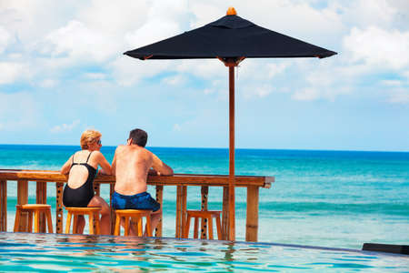 Successful retirement recreation, summer vacation concept. Retired mature couple enjoying beautiful sunny day in swimming pool at beach club. Happy senior woman and man sitting at poolside beach bar.