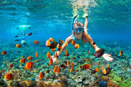 Happy family - couple in snorkeling masks dive deep underwater with tropical fishes in coral reef sea pool. Travel lifestyle, outdoor water sport adventure, swimming lessons on summer beach holiday Фото со стока