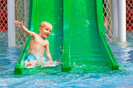 Funny happy baby boy have fun, sliding with splashes in blue swimming pool. Family summer lifestyle, children with parents water sports activity in aqua park on holidays. photo