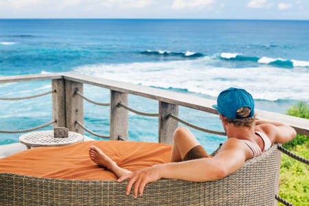 Young surfer relaxing in lounge on roof veranda with beautiful tropical sea view. Positive man look at ocean surf, enjoy vacation. Healthy lifestyle, people on family summer beach holiday. Stock Photo