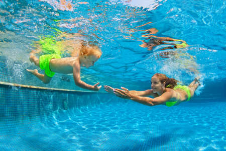 Happy family - mother, baby son learn to swim. Girl dive in swimming pool with fun - jump underwater with splashes. Lifestyle, summer children water sports activity, swimming lessons with parent.