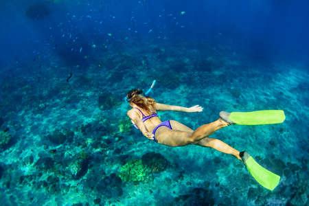 Gelukkige familie - meisje in snorkelen masker duiken onderwater met tropische vissen in koraalrif zee zwembad. Reis lifestyle, watersport outdoor avontuur, zwemlessen op zomervakantie met kinderen Stockfoto