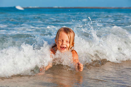 Happy family lifestyle. Baby girl splashing and jumping with fun in breaking waves. Summer travel, water sport outdoor activities, swimming lessons on tropical beach holiday with kids. Archivio Fotografico