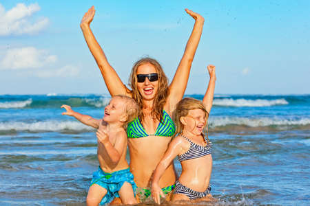 Happy family lifestyle. Young mother with children jumping and splashing with fun in breaking waves. Summer travel, water sport outdoor activities, swimming lessons on tropical beach holiday with kids