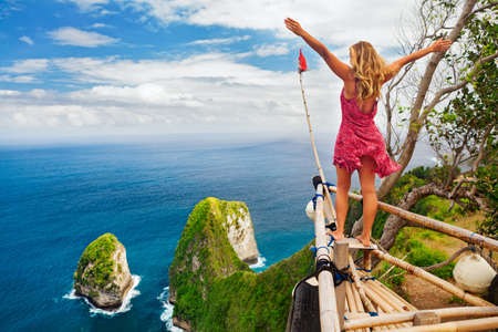 Family vacation lifestyle. Happy woman with raised in air hand stand at viewpoint. Look at beautiful beach under high cliff. Travel destination in Bali. Popular place to visit on Nusa Penida island Stockfoto