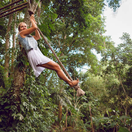 Family travel lifestyle. Happy young woman flying high with fun on rope swing on wild jungle background. Funny adventure walk in tropical rainforest. Leisure activity on summer vacation with kids. Stock Photo