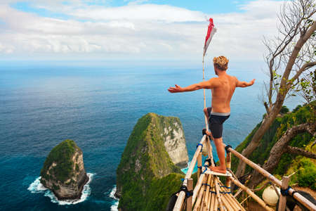 Family vacation lifestyle. Happy man with raised in air hand stand at viewpoint. Look at beautiful beach under high cliff. Travel destination in Bali. Popular place to visit on Nusa Penida island