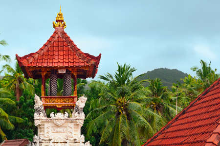 Wooden bells kulkul on traditional belfry with carving on white limestone walls. Balinese hindu temple on jungle and rainy sky background. Nusa Penida island landmarks. Culture of Indonesian people. Stock fotó - 83295350