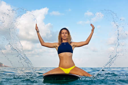 Happy girl in bikini have fun before surfing. Surfer sit on surf board and splashing. People in water sport adventure camp, beach extreme activity on family summer beach vacation. Waterport background