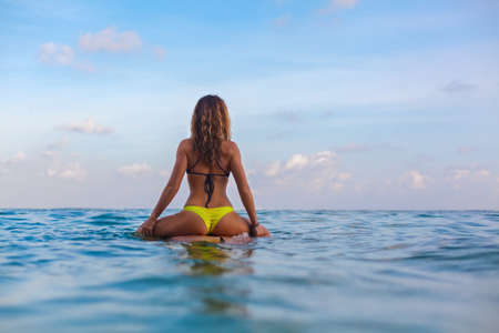 Happy girl in bikini have fun before surfing Surfer sit on surf board, look at sunset sky. People in water sport adventure camp, extreme activity on family summer beach vacation. Watersport background Banque d'images