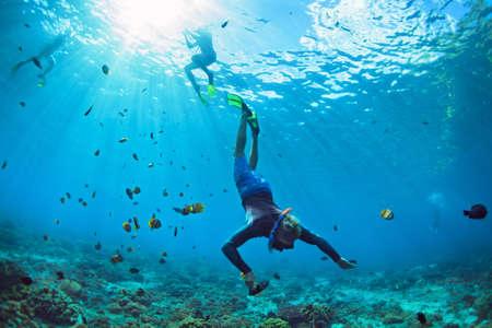 Gelukkige familie vakantie. Man in snorkelen masker met camera duiken onder water met tropische vissen in koraalrif zee zwembad. Reis lifestyle, watersport buitenavontuur, zwemmen op zomervakantie Stockfoto