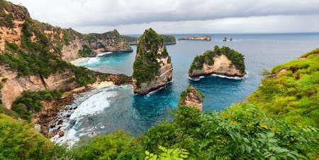 높은 절벽에 서있는 작은 집과 바다 해안보기 바다와 작은 바위 섬 위에 가져온다. Atun 해변, 누사 Penida 섬입니다. 발리 휴일에 인기있는 여행 목적지.