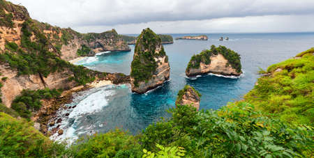 Sea coast view with little house standing on the high cliff bring above sea and little rocky islets. Atun beach, Nusa Penida island. Popular travel destination on Bali holidays. Indonesian background.