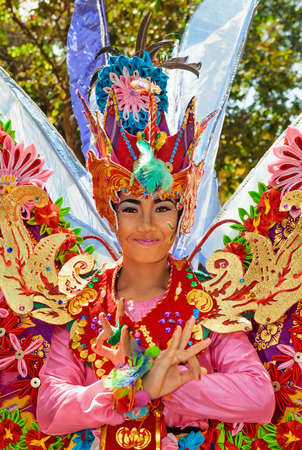 DENPASAR, BALI ISLAND, INDONESIA - JUNE 11, 2016: Beautiful dancer woman in traditional costumes dance on street parade at art and culture festival. Balinese people portrait Stock Photo - 84380620