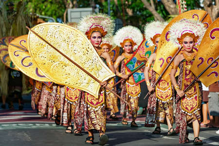 DENPASAR, BALI ISLAND, INDONESIA - JUNE 11, 2016: Group of Balinese people. Beautiful dancer women in traditional costumes dance on street parade at art and culture festival. Editorial