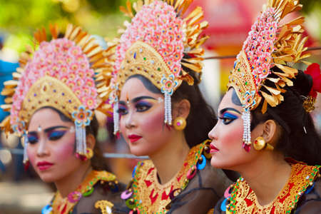 DENPASAR, BALI ISLAND, INDONESIA - JUNE 10, 2017: Group of Balinese people. Beautiful dancer women in traditional costumes on street parade at art and culture festival.