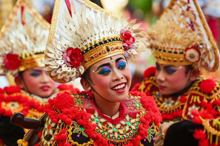 DENPASAR, BALI ISLAND, INDONESIA - JUNE 10, 2017: Group of Balinese children. Beautiful young dancers in traditional costumes on street parade at art and culture festival.