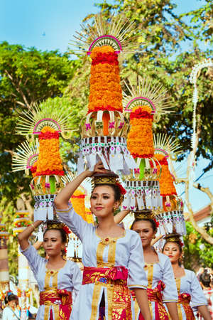 DENPASAR, BALI ISLAND, INDONESIA - JUNE 11, 2016: Group of beautiful women in traditional Balinese costumes carry on head religious offering for hindu ceremony on parade at art and culture festival. Banco de Imagens - 84380625