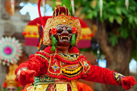 Dancer man in traditional Balinese costume and monkey mask - character of Bali island culture. Temple ritual dance at ceremony before religious holiday. Ethnic festivals, arts of Indonesian people.