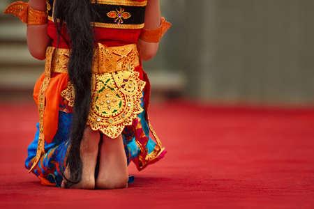 Aziatische reisachtergrond. Mooi Balinees dansersmeisje met naakte voeten in traditionele Sarong-kostuum dansende Legong-dans. Kunst, cultuur van Indonesische mensen, etnische feesten op het eiland Bali. Stockfoto