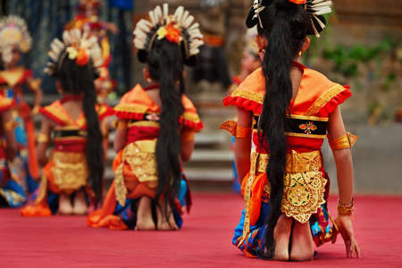 Asian travel background. Group of beautiful Balinese dancer girls with bare feet in traditional Sarong costume dancing Legong dance. Arts, culture of Indonesian people, Bali island ethnic festivals.