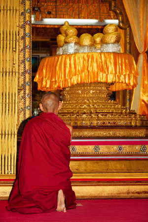 Monk praying in front of shrine with sacred Buddha figures covered by gold leaves in buddhist temple Hpang Daw U on Inle lake in Myanmar. Traditional arts, culture and religion of Burmese people. Imagens - 84961600