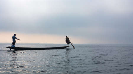 Black silhouette of two fishers standing on stern and paddling by legs, travelling by traditional long boat on Inle lake, Myanmar. Culture and traditions of Burmese people. Asian travel background. Stock Photo