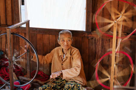 Inle Lake, Myanmar - January 04, 2007: Old woman of Intha people working at home in village on Inle lake in Shan state, spinning yarn by hand for traditional Burmese handmade textile.