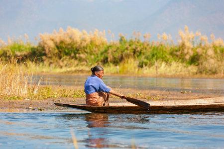 インレー湖、ミャンマー-1 月04、2007: ミャンマーの古い女性は、伝統的なフローティングガーデンでの仕事から彼女の村、Nyaungshwe 湖の近くにありま