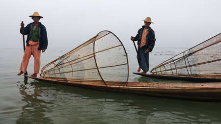 paddles: Inle Lake, Myanmar - January 04, 2007: Two local fishers with traditional Burmese fishing nets standing on stern of long boats and rowing oars by leg, on Inle lake, Shan state, Myanmar. Editorial