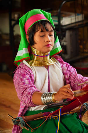 Inle Lake, Myanmar - January 04, 2007: Young woman of Kayan Lahwi (Padaung) people wearing brass coils on long neck weaving traditional Burmese handmade textile in village on Inle lake in Shan state.