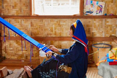 Inle Lake, Myanmar - January 04, 2007: Young woman of Kayan Lahwi (Padaung) people wearing brass coils on long neck weaving traditional Burmese handmade textile in village on Inle lake in Shan state.